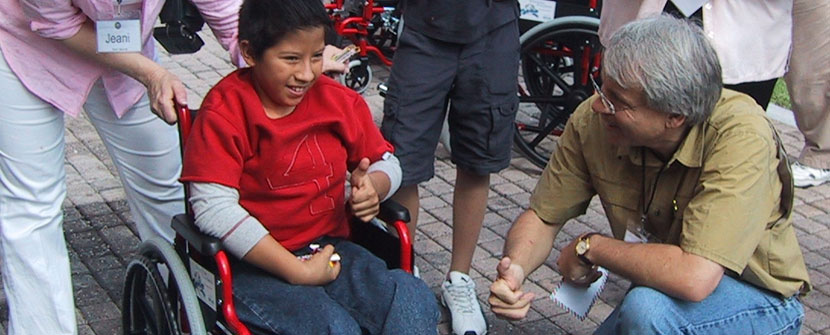 Mike with boy receiving new wheelchair